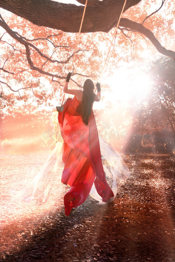 Girl on swing. A girl or young woman swinging outside in a long formal gown or dress with long brown hair looking off into the distance with the sun beaming down royalty free stock photos