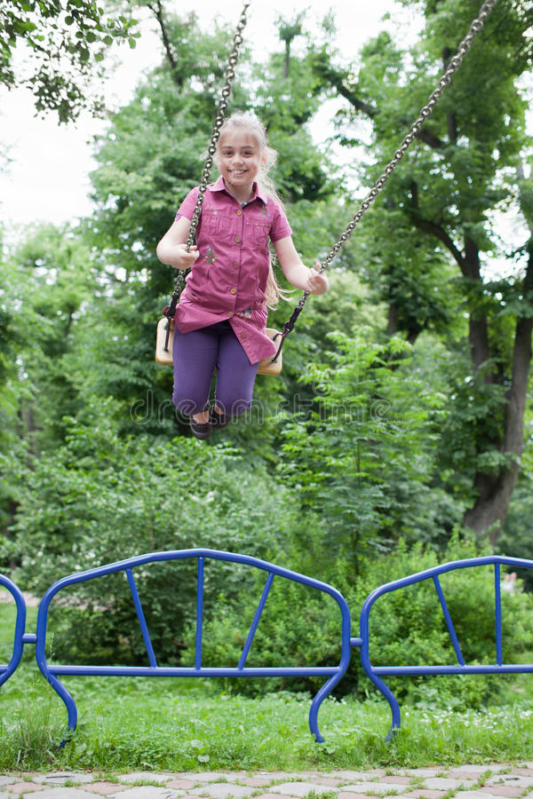Girl swinging with a big smile royalty free stock image