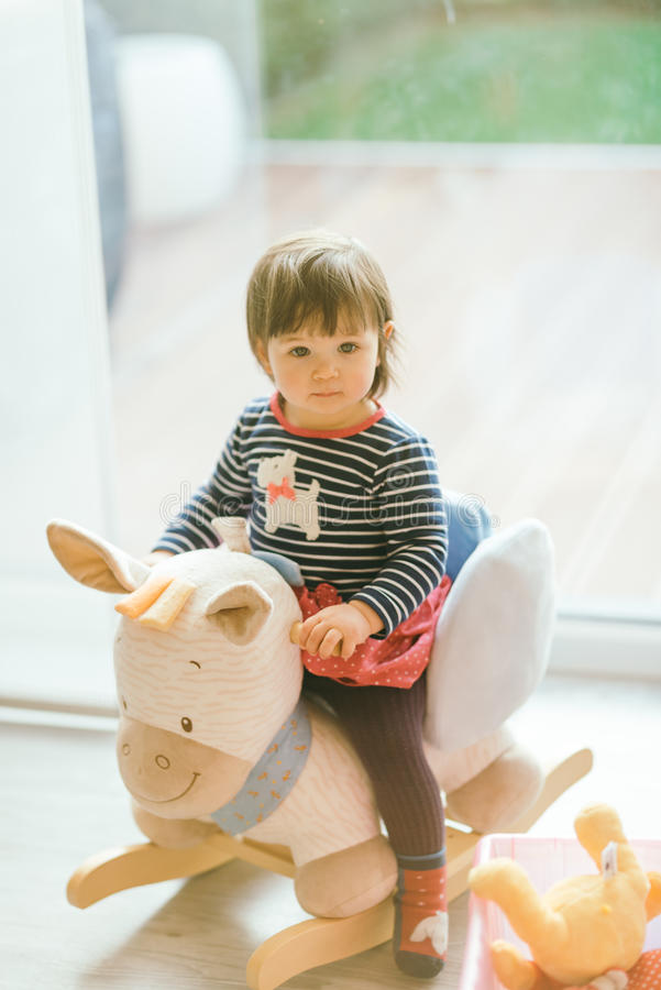 Girl swinging on a rocking horse royalty free stock images