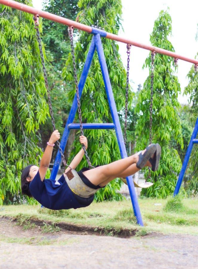 Girl swinging swing in the garden. royalty free stock image