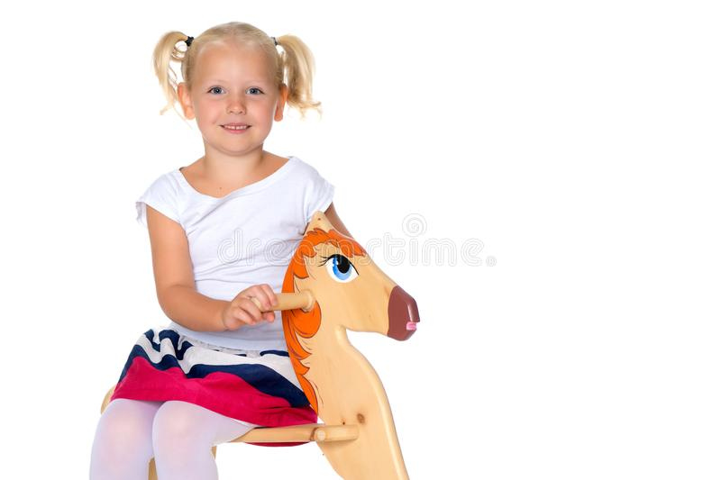 Girl swinging on a wooden horse. stock images