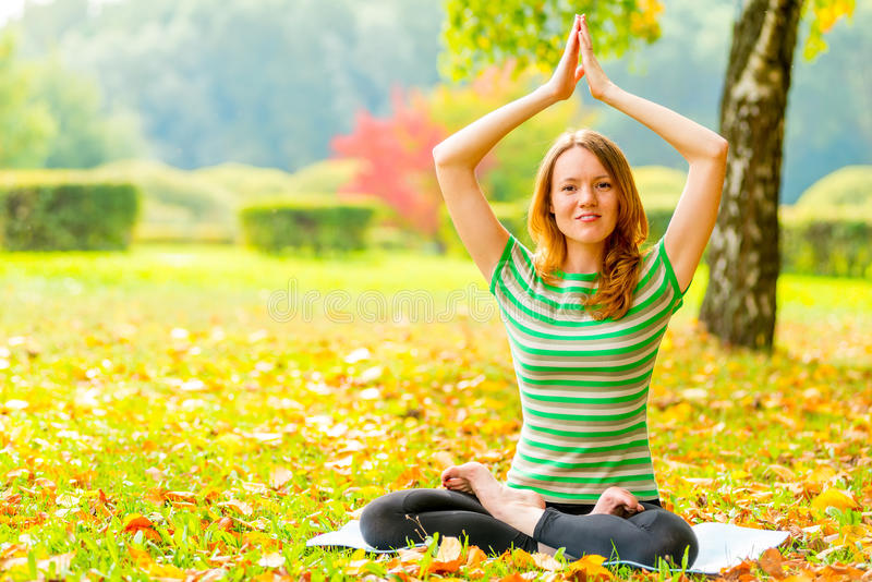 Girl in a T-shirt in autumn park doing exercises stock photography