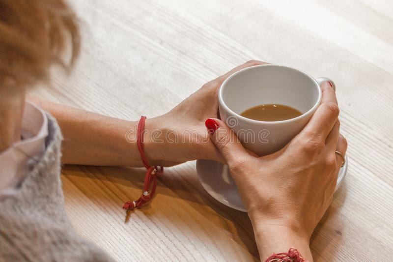 The girl at the table in a cafe with a cup of coffee. White cup of coffee in female hands. Warm your hands with a cup of hot drink. Meeting in a cafe. The girl royalty free stock images
