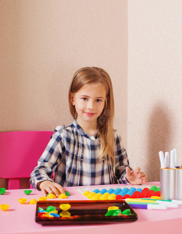 Girl at the table with mosaic stock photography