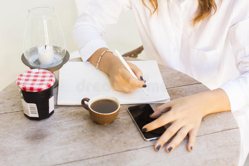 Girl at the table writing in a notebook with a cell phone and te. A, close up royalty free stock photos