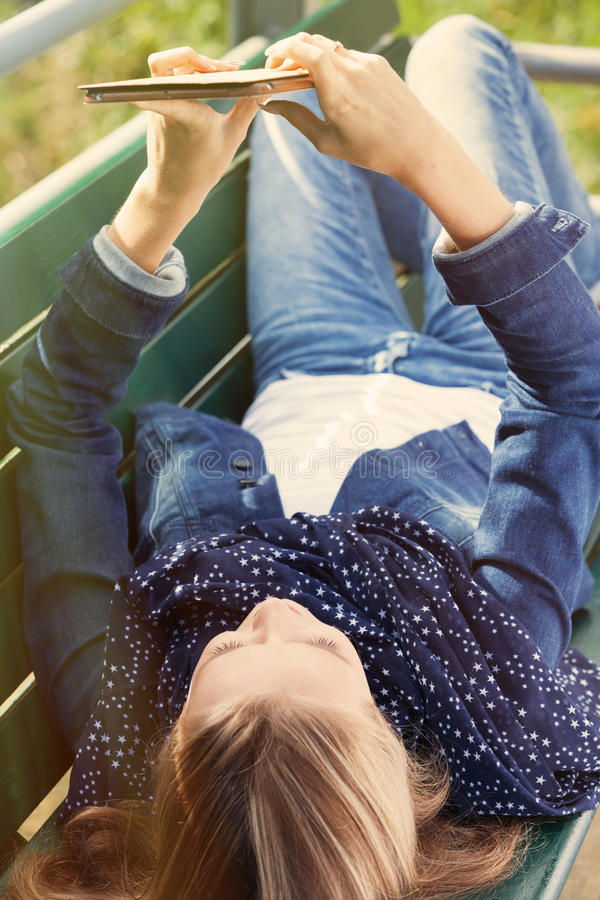 Girl with tablet PC. Laying on the bench in the park royalty free stock photography