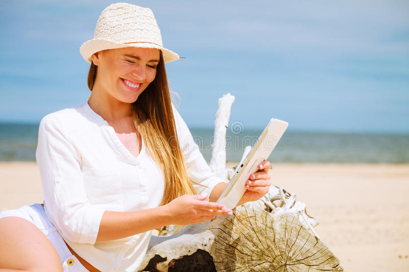 Girl with tablet on seaside. Technology enjoyment. Long haired beauty girl in straw hat with tablet e-book on beach. Student woman resting in summer on fresh stock image