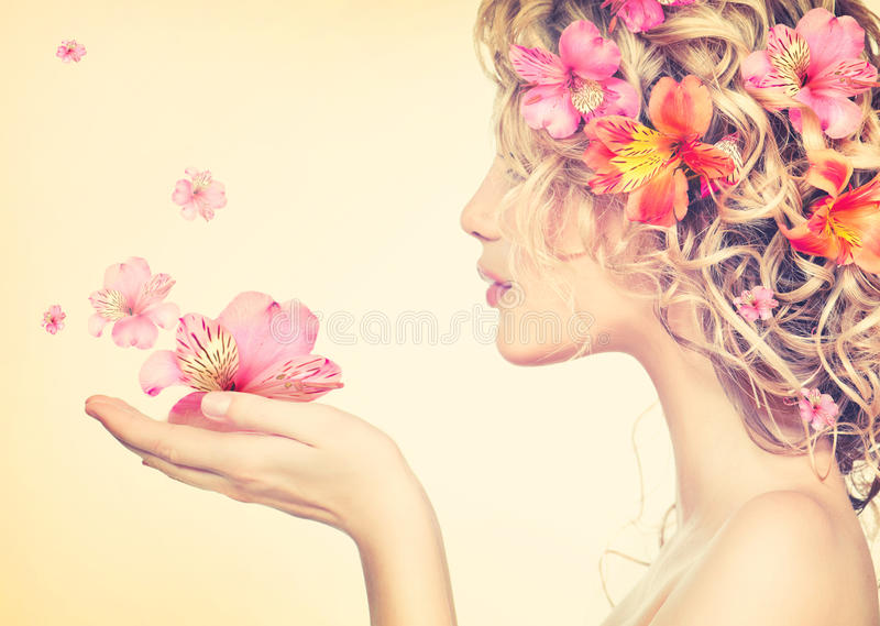 Girl takes beautiful flowers in her hands. Blowing flower stock images