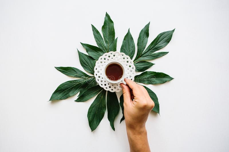 The girl takes a cup of useful fragrant tasty herbal or black tea is going to drink it. royalty free stock photography