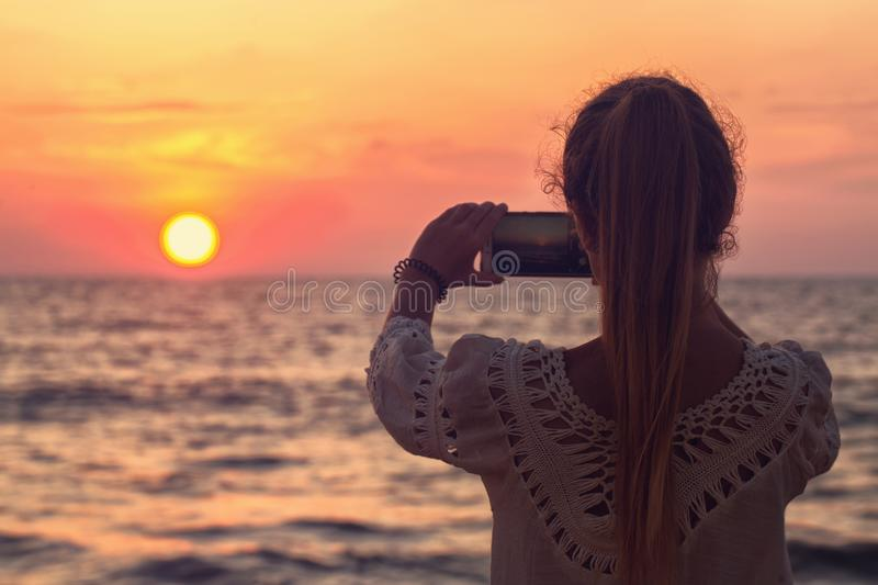 A girl takes a picture of the sunset royalty free stock image