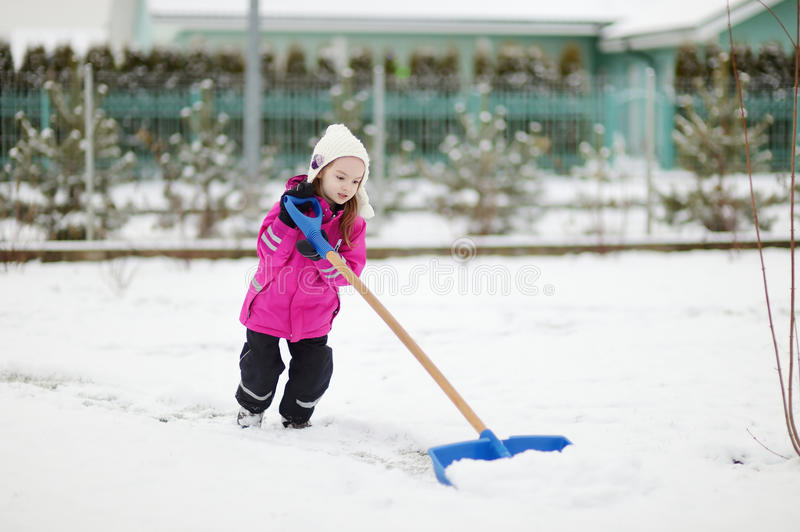 A girl takes pride in completing a shoveling job stock images