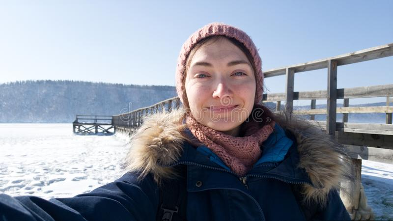 The girl takes a selfie against a wooden pier. Winter river Angara. The winter journey through Siberia.  stock photography