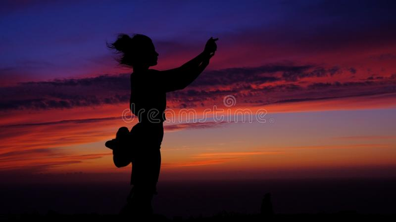 Girl takes a selfie at sunset. Silhouettes of the girl. Young, beautiful, girl photographs herself on a sunset background. Sea walk. Travel, photography at the royalty free stock photo