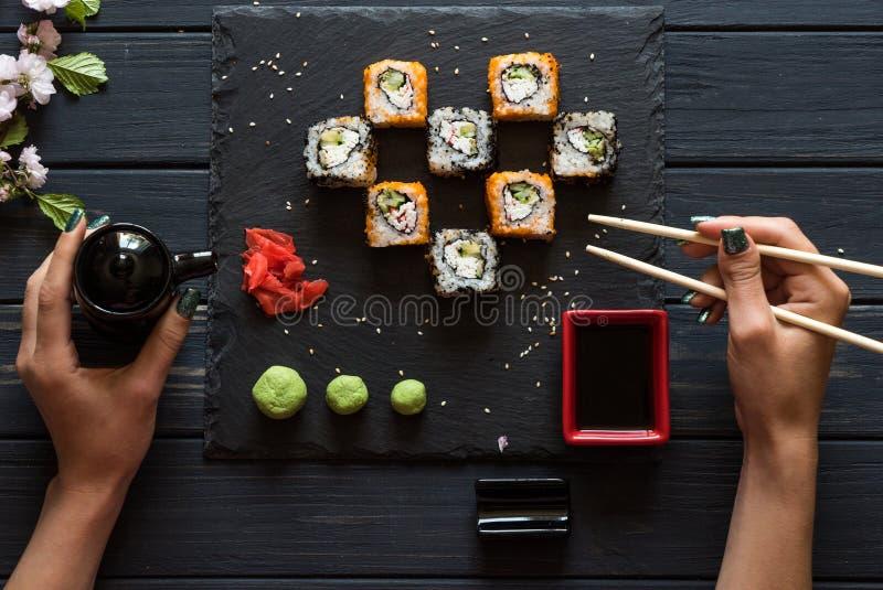 Girl takes sushi chopsticks stock images