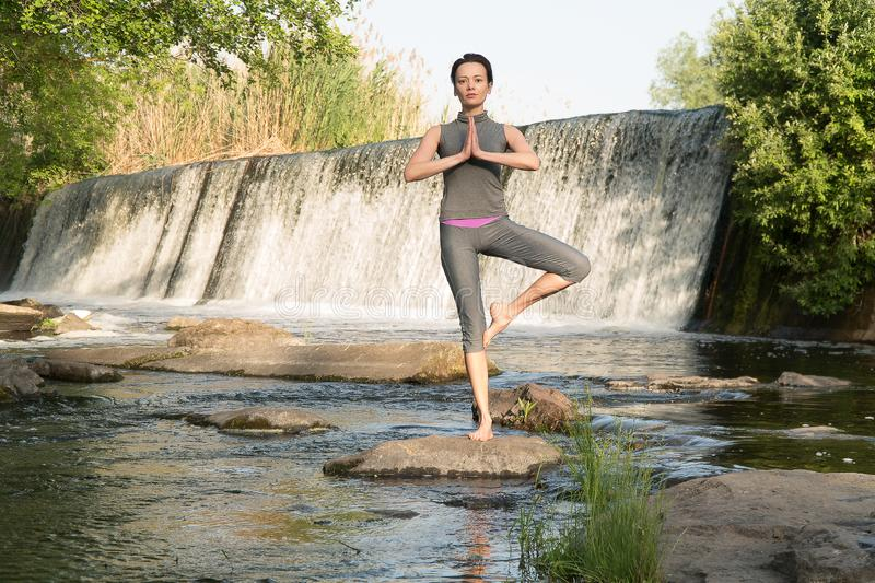 The girl takes up yoga by the water royalty free stock photo