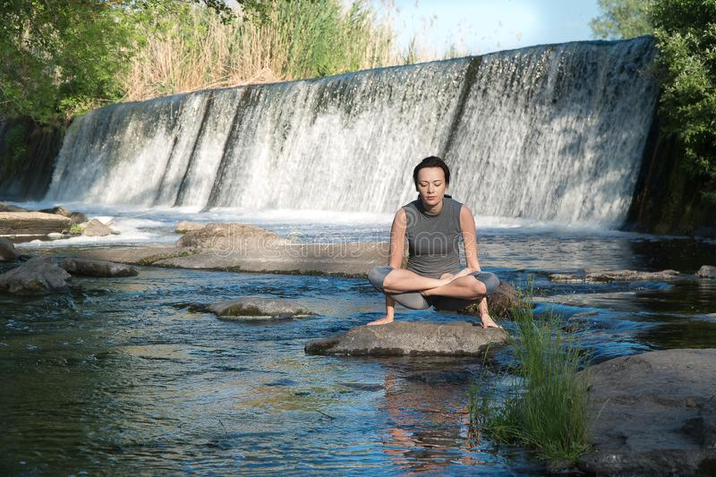 The girl takes up yoga by the water royalty free stock images