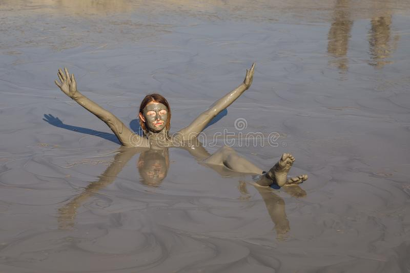 Girl takes useful procedures in an active mud volcano on a sunny day royalty free stock photos