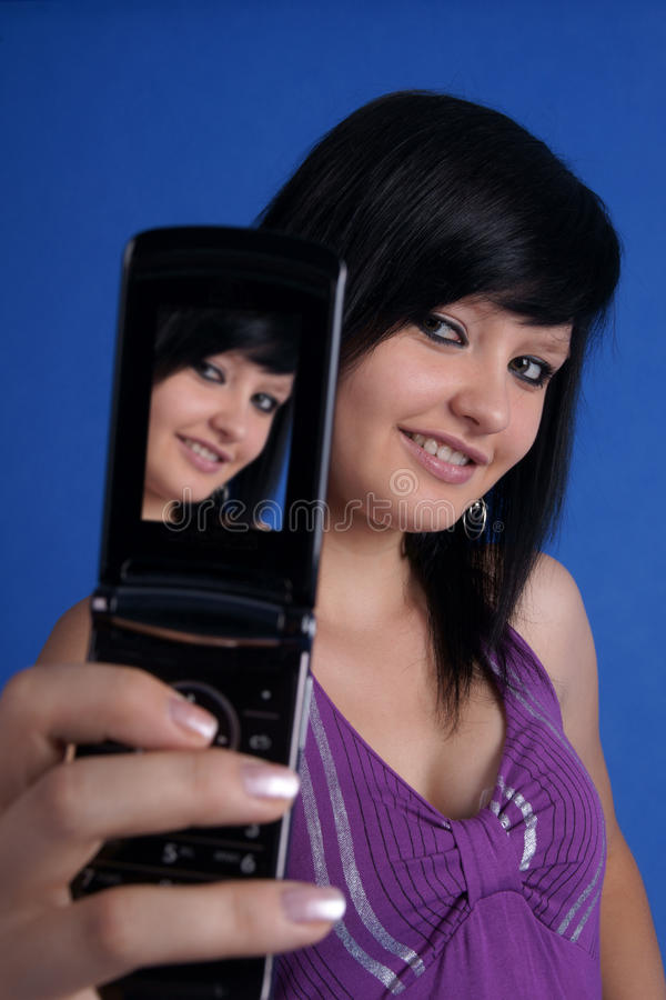 Girl taking auto portrait using mobile phone