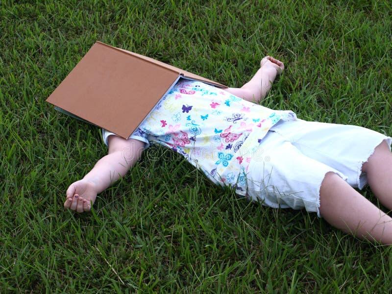 little girl lying in grass taking break under book royalty free stock photo