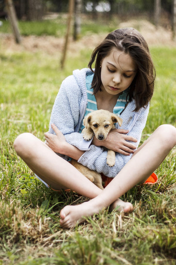 Girl taking care for a little puppy royalty free stock image