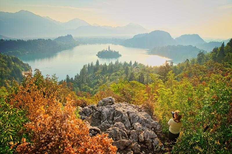 Girl is taking a landscape photo. Female photographer is taking photograpgh of dramatic scenic panorama of Bled lake in Slovenia Triglav national park. Europe stock image