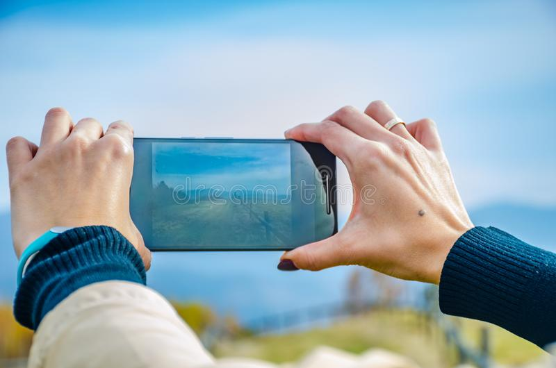 Girl taking a photo of carpathian mountains. royalty free stock photography