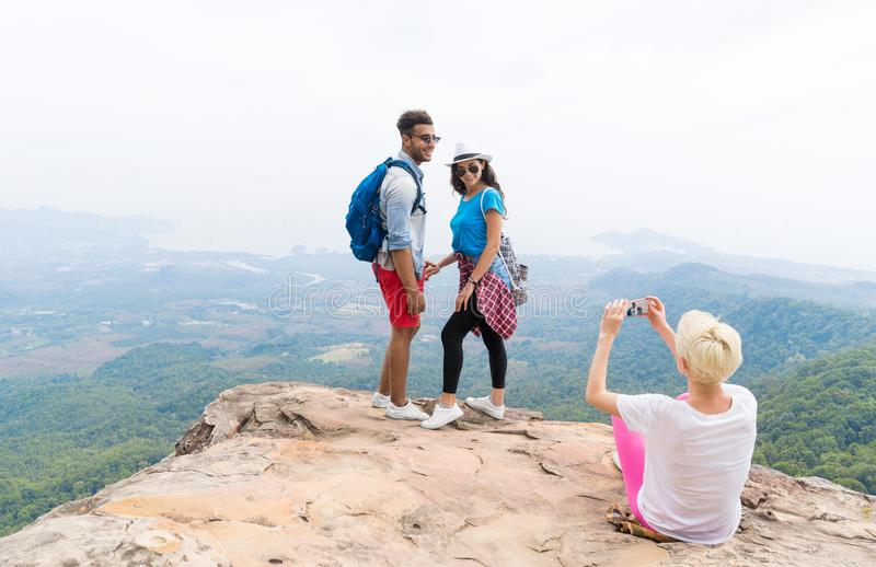 Girl Taking Photo Of Couple With Backpacks Posing Over Mountain Landscape On Cell Smart Phone, Trekking Young Man And royalty free stock photos