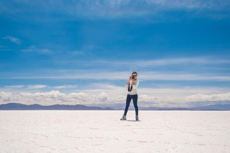 Girl taking photo in sunshine Salar de Uyuni royalty free stock image