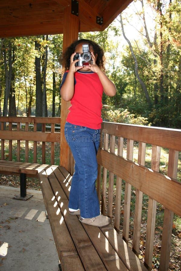 Girl taking photograph. Young multiracial girl stood on veranda taking photograph stock image
