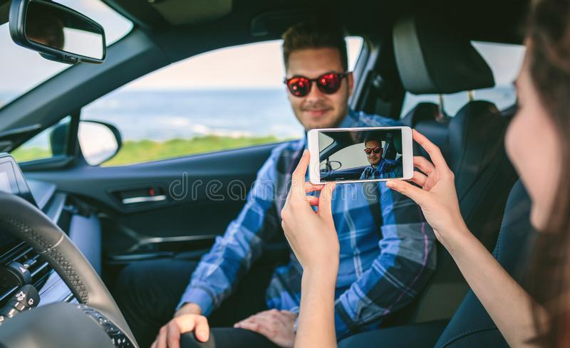 Girl taking picture with mobile to her boyfriend. Girl taking a picture with the cell phone to her boyfriend in the car. Selective focus on mobile in foreground royalty free stock images