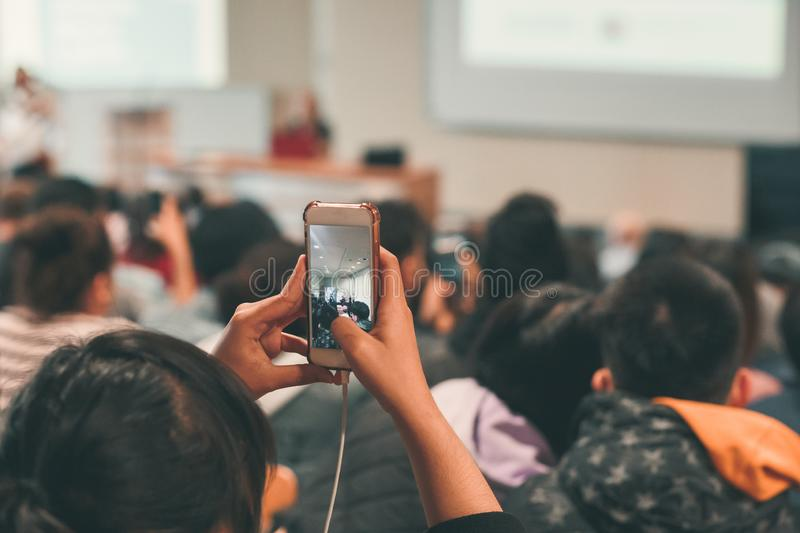 Girl taking picture of peaople using mobile phone. Rear view of girl taking picture of peaople using mobile phone. Visible smartphone screen stock photography