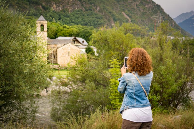 Girl taking a picture with a smartphone of the romanesque church of Sant Feliu de Barruera, in catalan Pyrenees. Girl taking a picture with a smartphone of the stock images