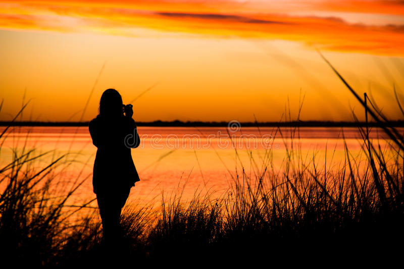Girl taking a picture of the sunset royalty free stock photo