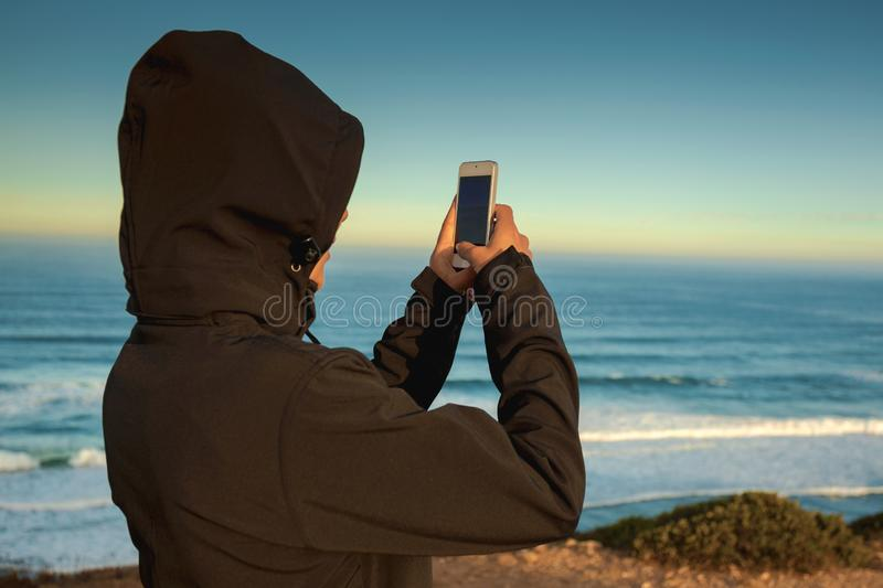 Girl taking a picture. Woman taking a picture to the beach with a cellphone stock photography