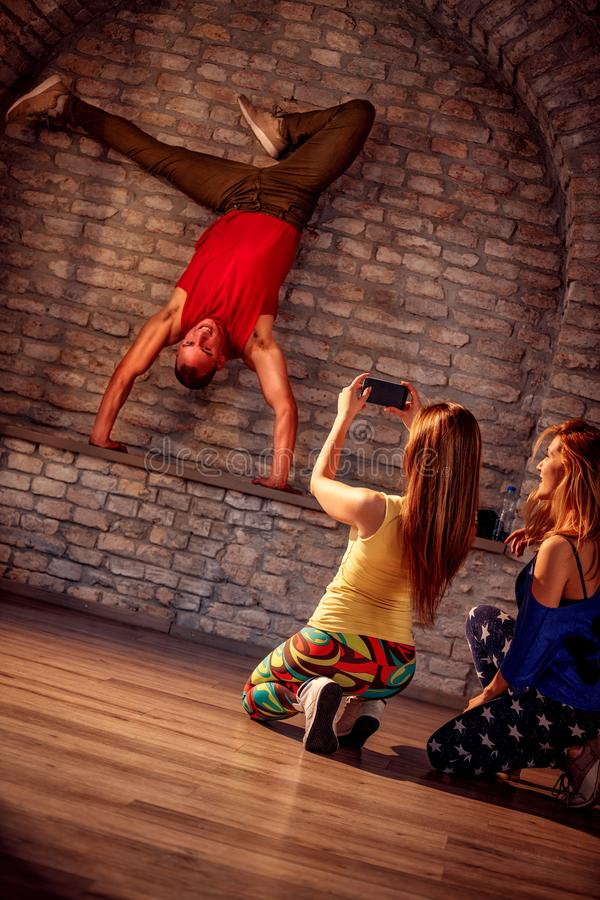 Girl taking picture of young street artist break dancing perform. Girl taking picture of young street male artist break dancing performing moves stock image