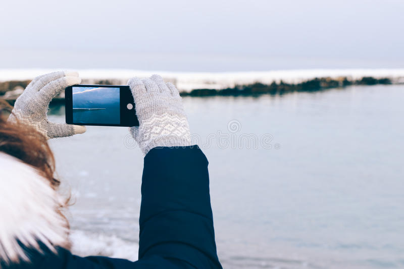 Girl taking pictures of the beach on a mobile phone in winter. Close-up royalty free stock photos