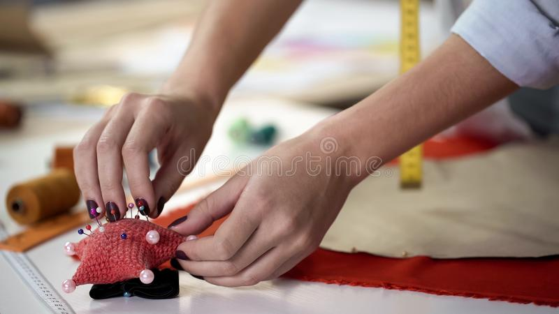 Girl taking pins from needles pad and fixing template on fabric before cutting stock photos