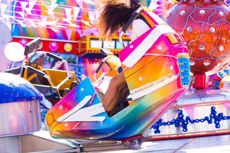 Girl taking a ride on break dance carousel in lina park, funfair royalty free stock photo