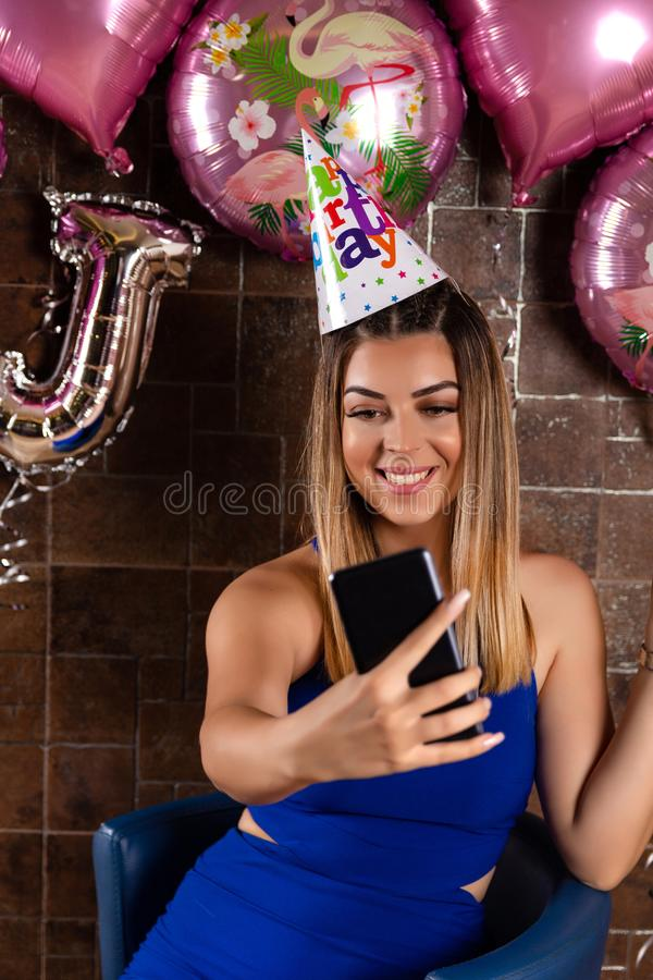 Girl taking a selfie and celebrating a birthday with a cap on head. Beautiful and cute young girl taking a selfie and celebrating a birthday with a cap on head royalty free stock image