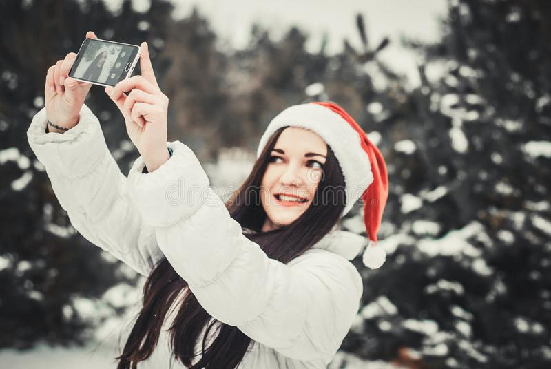Funny girl taking selfie. Christmas girl outdoor self portrait. Woman in winter clothes and claus hat on a snow field. Girl taking selfie. Christmas girl outdoor royalty free stock images