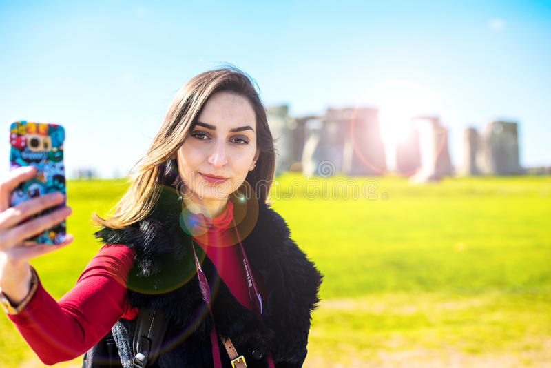 Girl taking a selfie i front of Stonehenge royalty free stock photos