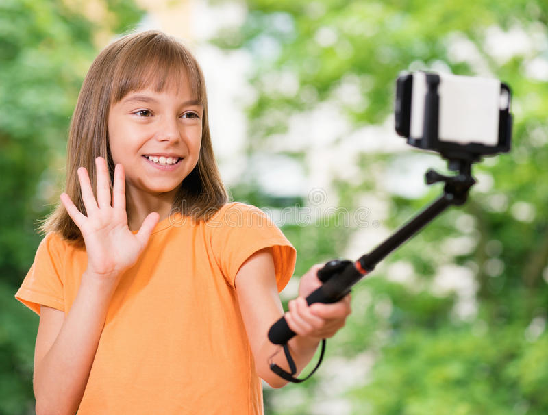 Girl taking selfie. Outdoors portrait of beautiful little girl taking a selfie at the park royalty free stock photography