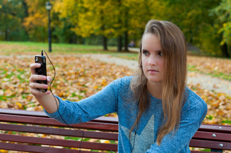 Girl taking selfie outdoors stock photography