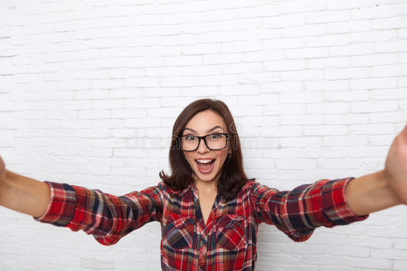 Girl Taking Selfie Smart Phone Photo Camera Excited. Happy Smile Woman Over White Brick Office Wall stock photography