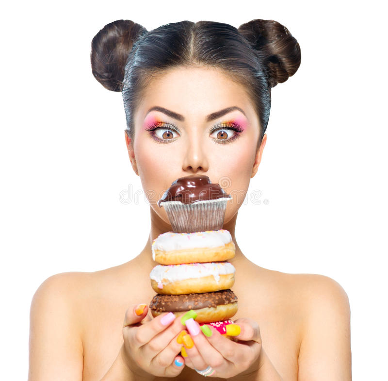 Girl taking stack of colorful donuts and muffin royalty free stock images