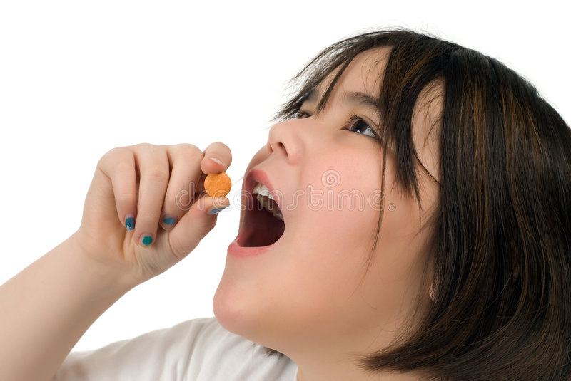 Girl Taking Vitamin C. A young girl taking a chewable vitamin c tablet, isolated against a white background royalty free stock photo