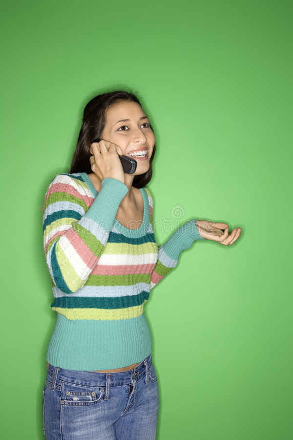Girl talking on cellphone. Portrait of Multi-racial teen girl talking on cellphone and smiling standing against green background royalty free stock images