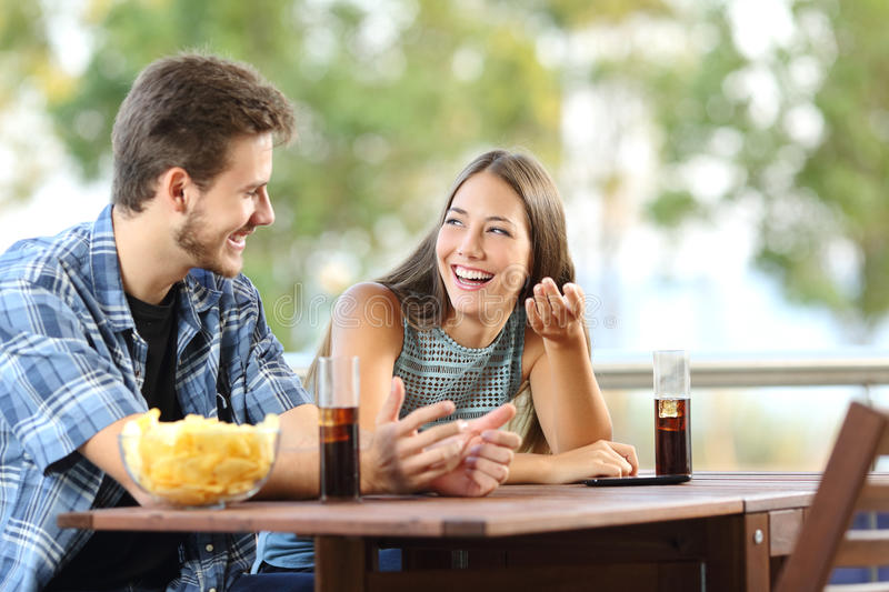 Girl talking with her friend in a terrace stock photos