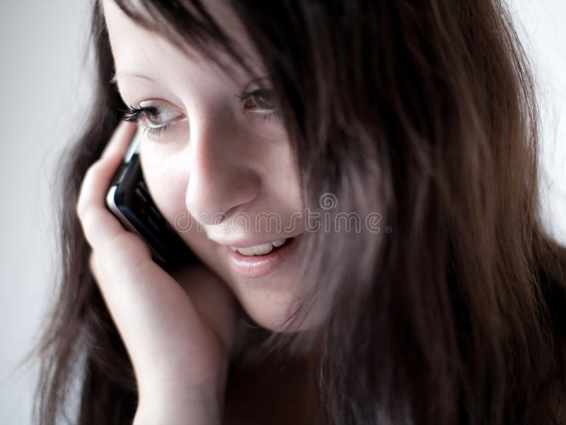 Girl talking on a mobile phone II. A girl/young woman talking on her mobile phone and smiling stock photo