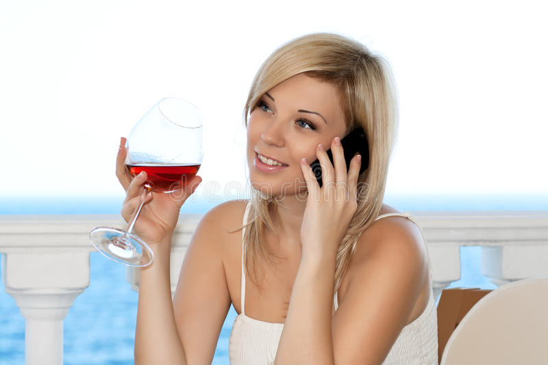 Girl talking on the phone in a cafe and drink wine stock image